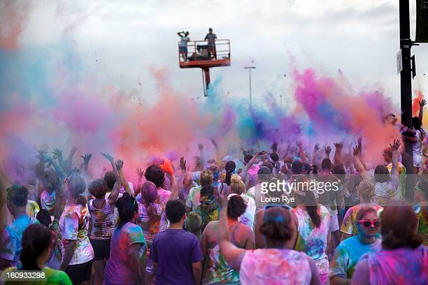 Participants in the Omaha, NE/Council Bluffs, IA Color Me Rad charity run throw colored powder up into the air in a final 'color bombing' cloud as...