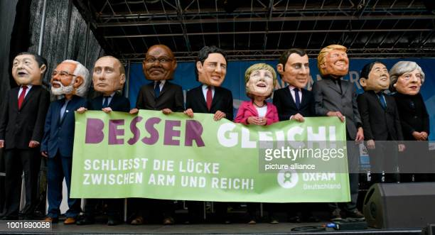 Participants in the protest wave against the G20 Summit pictured standing on stage wearing masks with the likeness of Chinese President Xi Indian...