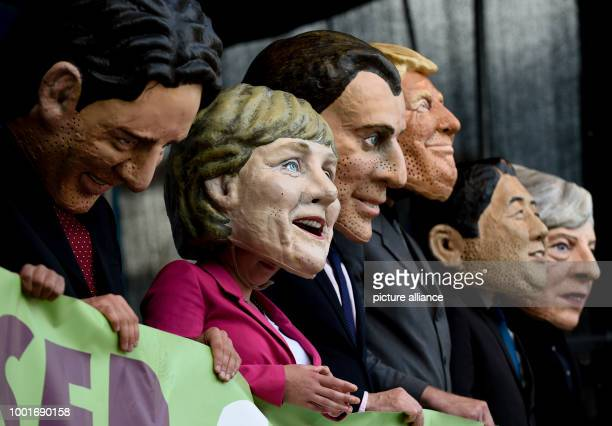 Participants in the protest wave against the G20 Summit pictured standing on stage wearing masks with the likeness of Canadian Prime Minister Trudeau...