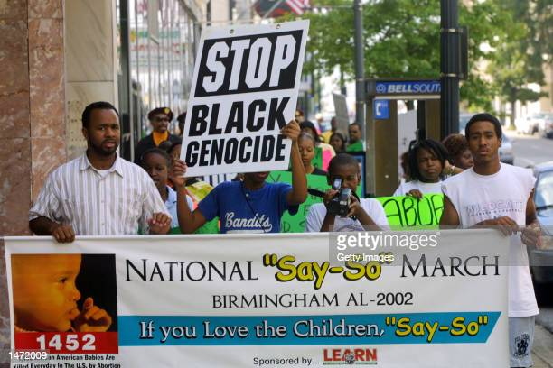 Participants in the Say So March hold signs and a banner as they participate in an antiabortion march October 12 2002 in downtown Birmingham Alabama...