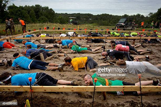 Participants in the Tough Mudder obstacle course a 103 mile trail run littered with obstacles and hazards compete in the 'Kiss the Mud' challenge...