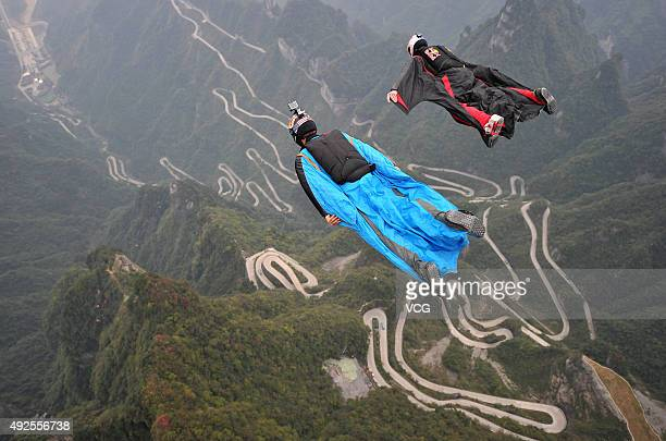 Participants in wingsuits fly above Tianmen Mountain at Zhangjiajie Scenic Spot during a test flying ahead of The 4th Red Bull WWL China Grand Prix...