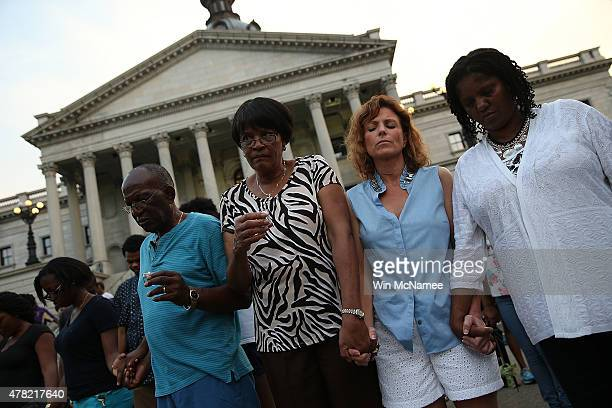 Participants link arms during a moment of silence at a memorial service for the nine victims of last week's shooting at Emanuel African Methodist...