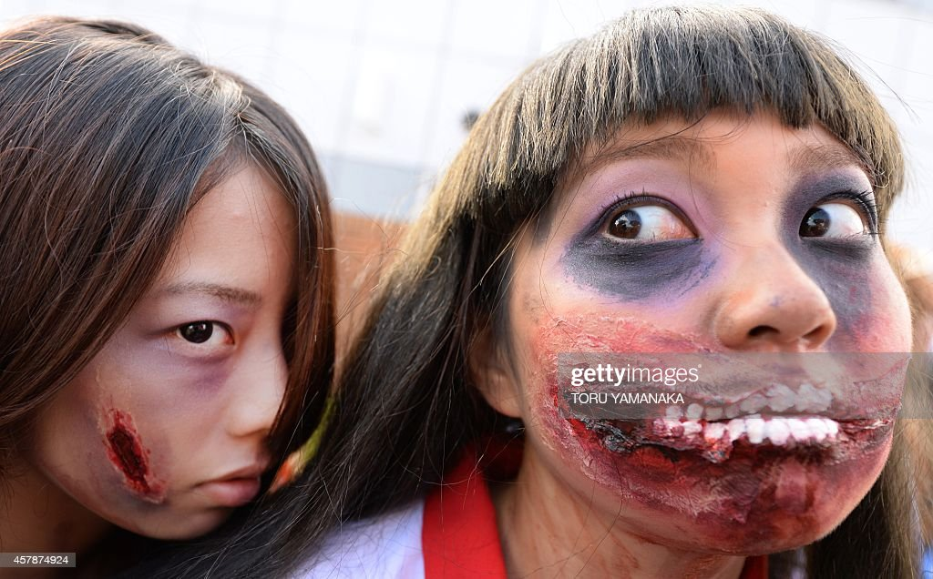 Participants make up as they pose for pictures before the Halloween Parade in Kawasaki, a suburb of Tokyo, on October 26, 2014. More than 100,000 visitors watched the street costume parade in which some 2,500 people took part. AFP PHOTO/Toru YAMANAKA
