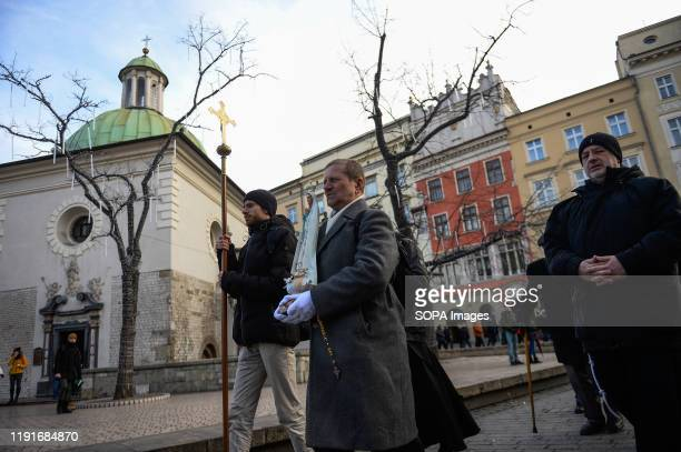 Participants march while carrying a cross and a statue of Our Lady of Fatima during the monthly Men's Rosary at the Main Square in Krakow Few dozens...