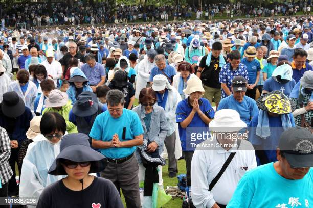 Participants observe a minute of silence for late Okinawa Prefecture Governor Takeshi Onaga during a rally at Onoyama Athletic Stadium on August 11...
