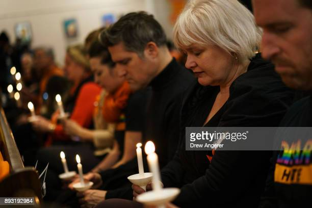 Participants observe a moment of silence as they hold candles during a vigil to mark the 5th anniversary of the 2012 mass shooting at Sandy Hook...