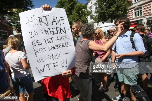Participants of a cleaning campaign discuss with people who seem to oppose the cleaning in front of the Rote Flora cultural center in Hamburg Germany...