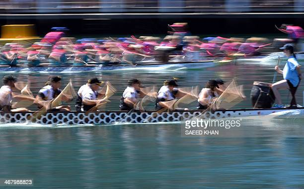 Participants of a dragon boat race power their boats on the Darling Harbour in Sydney on February 9 2014 The Chinese New Year Dragon Boat Races saw...