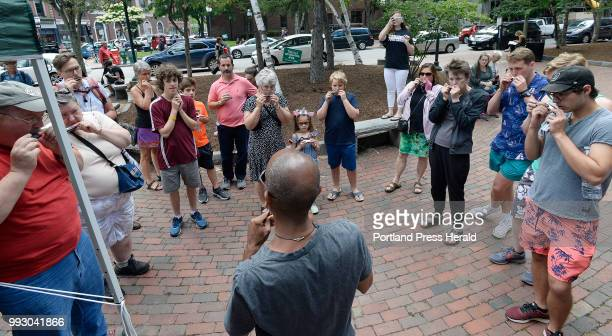 Participants of a harmonica lessons and jam session listen as Aaron Seglin center gives instructions at Post Office Plaza Thursday June 21 2018...