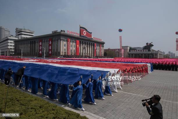 Participants of a mass rally carry a giant North korean flag as they pass through Kim IlSung square following a military parade marking the 105th...