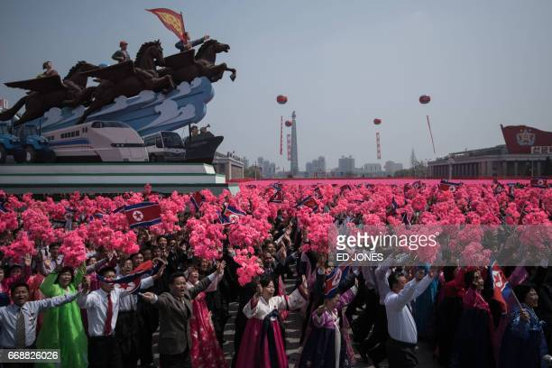 Participants of a mass rally wave flowers and shout slogans as they pass through Kim IlSung square following a military parade marking the 105th...