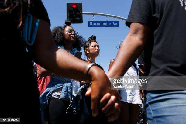 Participants of a peace rally at the intersection of Florence and Normandie hold hands and pray before marching on the 25th anniversary of the LA...