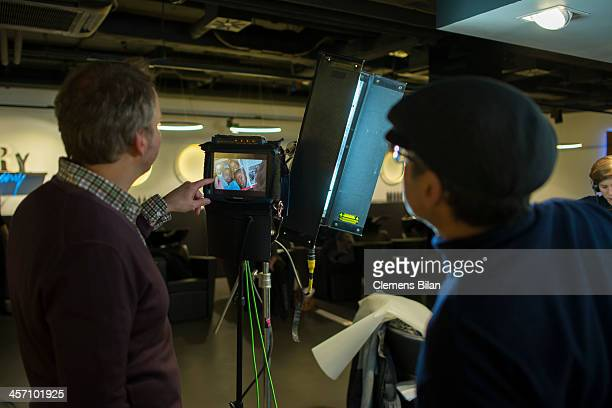 Participants of a shoot for AMREF in Salon Shan Rahimkhan check a monitor on December 16 2013 in Berlin Germany