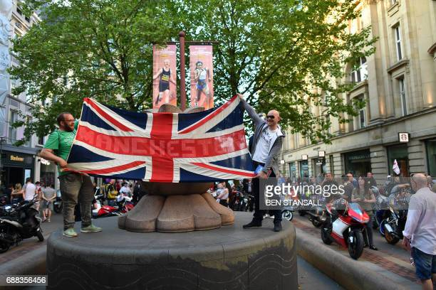 Participants of a Vespa Scooter Rally in memory of fifteen yearold terror attack victim Olivia Campbell hold up a Union Jack flag as they park in St...