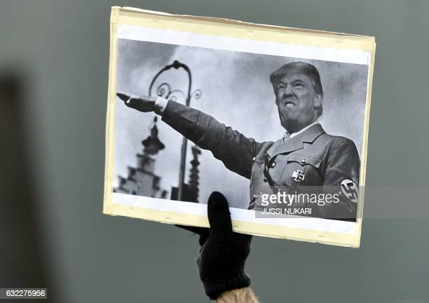 Participants of a Women's March in Helsinki carry a poster depicting US President Donald Trump in a nazi uniform on January 21 one day after the...