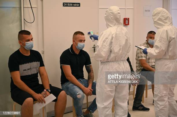 Participants of an exercise wear protective suits as they control the temperature of presumed patients at the Kutvolgyi hospital in Budapest,...