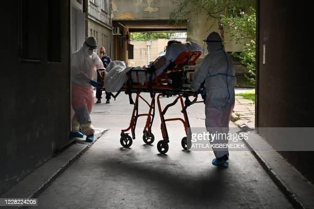 Participants of an exercise wear protective suits as they transport a presumed patient to the Kutvolgyi hospital in Budapest, Hungary, on August 27...