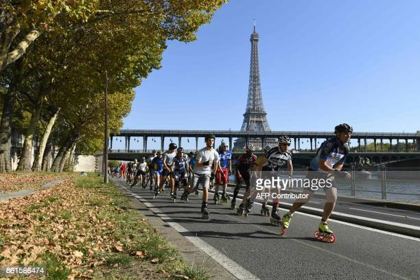 Participants of Paris Rollers Marathon skate along the Seine river with the Eiffel tower in background in Paris on October 15 2017 / AFP PHOTO / ERIC...