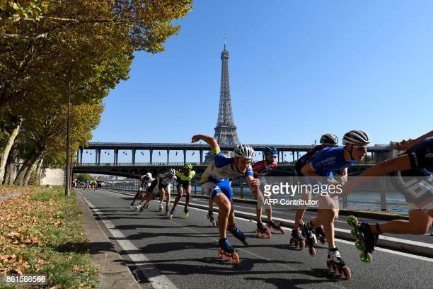TOPSHOT Participants of Paris Rollers Marathon skate along the Seine river with the Eiffel tower in background in Paris on October 15 2017 / AFP...