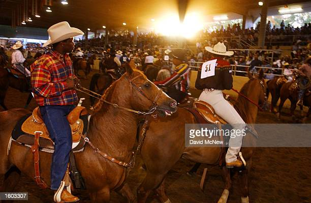 Participants of the 18th annual Bill Pickett Invitational Rodeo ride their horses at the start of the event July 21 2001 in Los Angeles CA The rodeo...
