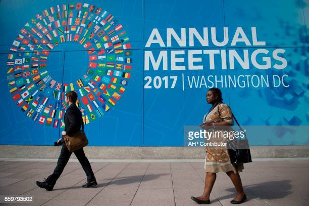 Participants of the 2017 Annual Meetings walk past a sign outside of the International Monetary Fund headquarters during the 2017 IMF Annual Meetings...