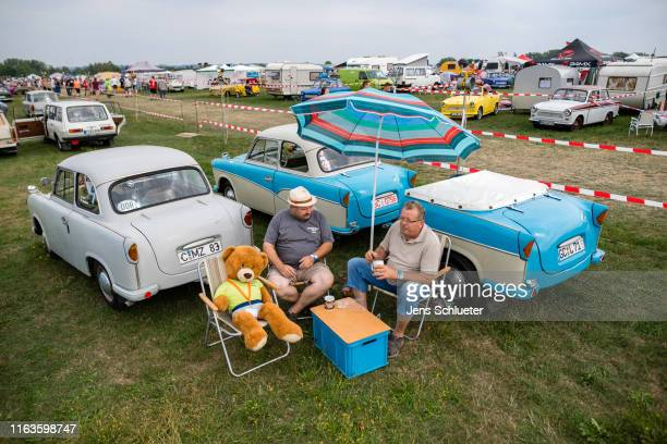 Participants of the annual meeting of the Trabant fans sit next to two Trabant on August 24 2019 in Zwickau Germany The humble Trabant or Trabi as...