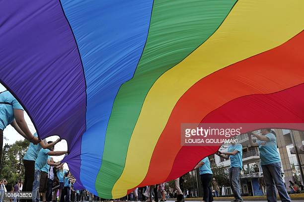 Participants of the Athens Gay Pride parade wave a giant rainbow flag during their annual march in the city's center on June 3 2010 Three thousand...