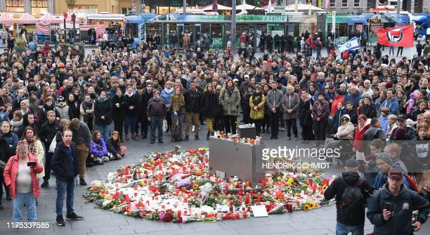 Participants of the demonstration Halle against Farright alliance for civil courage gather around a makeshift memorial for the victims of a deadly...