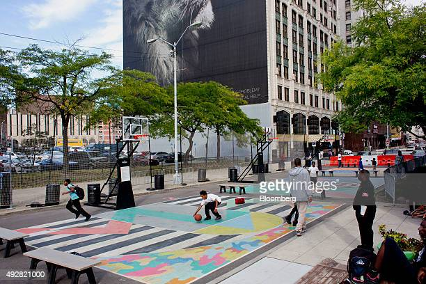 Participants of the Detroit Sports Zone a nonprofit social organization play basketball at Campus Martius Park in downtown Detroit Michigan US on...