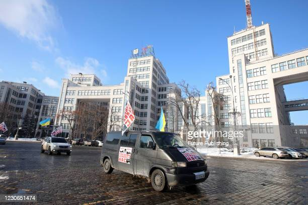 Participants of the Give Clean Air Back to Us car rally against the Kharkiv Coke Chemical Plant pass the Derzhprom building in Kharkiv, northeastern...