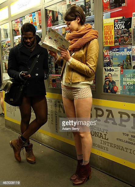 Participants of the No Pants Subway Ride wait at a newspaper kiosk in a station for a train on January 12 2014 in Berlin Germany The annual event in...