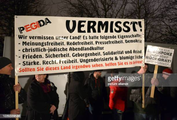 Participants of the Pegida group hold up a banner as they march during a rally in Dresden Germany 5 January 2015 The banner reads 'PEGIDA Missing We...