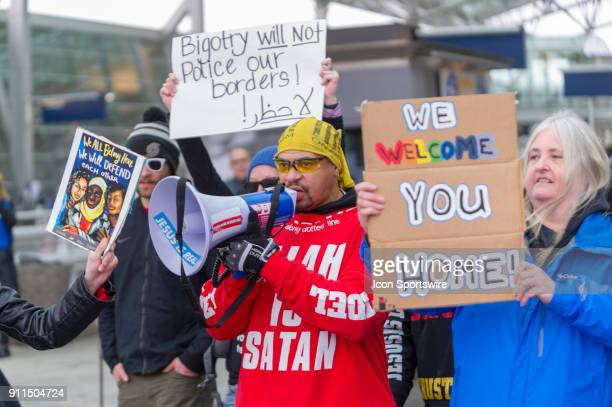 Participants of the Protest The Muslim Refugee Ban attempts to drown Quincy Lee Amatello's hate speech on the bullhorn at Portland International...