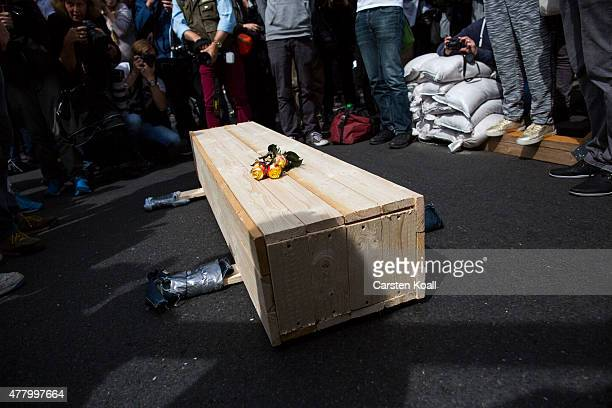 Participants of the rally gather around a symbolic coffin in front of the German Parliament Building on June 21 2015 in Berlin Germany A German...