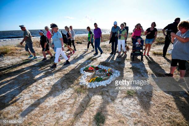Participants of the Run for Kim charity run in memorial of murdered Swedish journalist Kim Wall walk past a heartshaped makeshift memorial on August...
