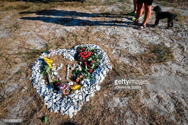 Participants of the Run for Kim charity run in memorial of murdered Swedish journalist Kim Wall stand next to a heartshaped makeshift memorial on...
