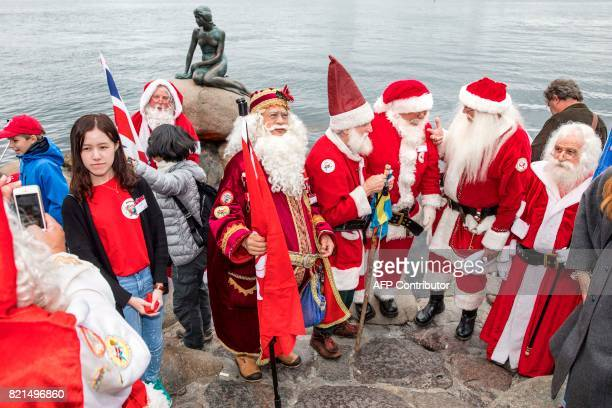 Participants of the Santa Claus World Congress visit the Little Mermaid statue in Copenhagen Denmark on July 24 2017 The first Santa Claus World...