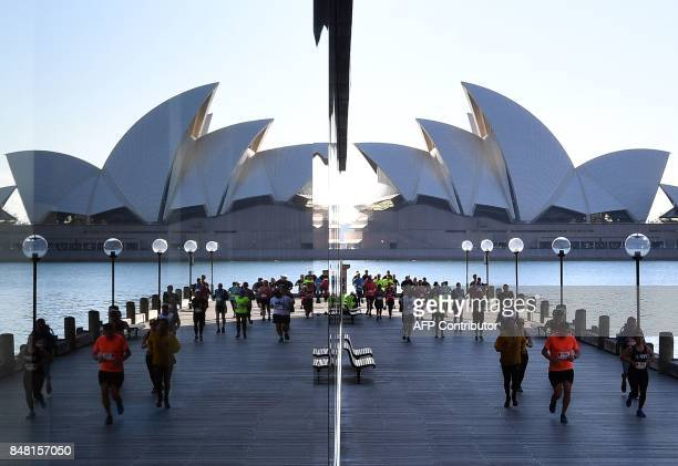 Participants of the Sydney marathon are reflect in a glass panel in front of the Opera House on September 17 2017 More then 33000 runners took part...