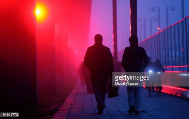 Participants of the United Nations Climate Change Conference walk past a bridge that is illuminated with red light next to the Bella Center on...