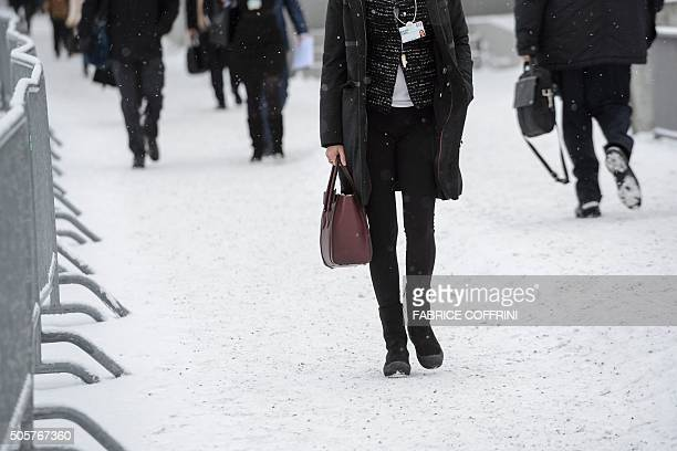 Participants of the World Economic Forum annual meeting walk in a snowcovered road in Davos on January 20 2016 A string of jihadist attacks and...