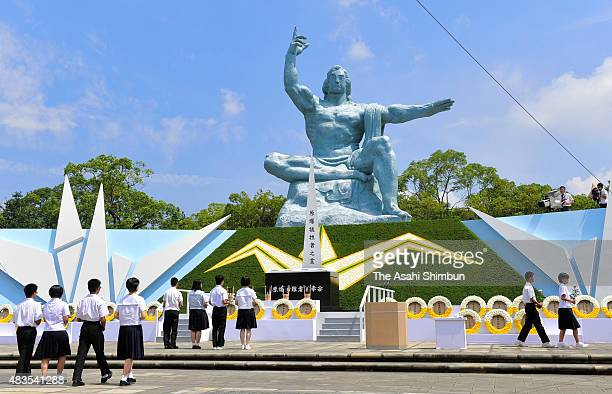 Participants offer flower bunches at an altar during the 70th anniversary peace memorial ceremony of the Nagasaki Atomic Bomb at the Nagasaki Peace...