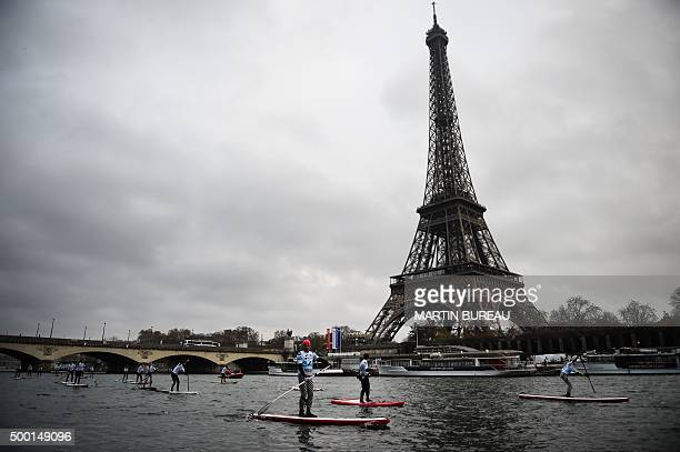 Participants paddle past The Eiffel Tour during a paddleboat race on the River Seine in Paris on December 6 2015 / AFP / MARTIN BUREAU