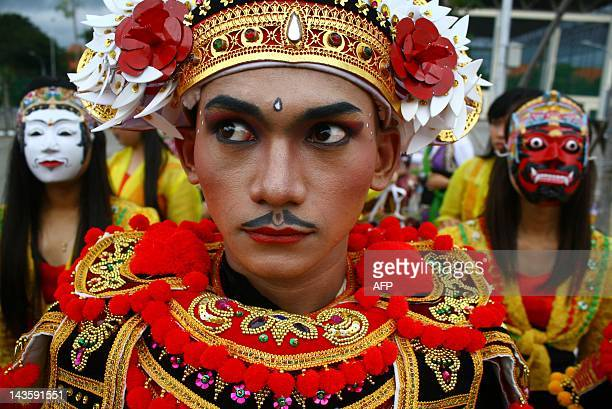 Participants parade in the street wearing traditional Indonesian masks and costumes during the national mask festival in Malang city in East Java...