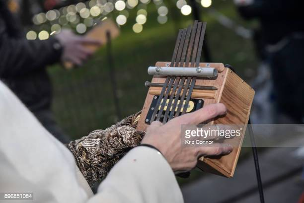 Participants participate in an ephemeral thumbpiano parade through Madison Square Park during the Kalimbascope event as part of Make Music Winter...