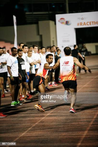 Participants pass the baton during the Dubai Dash 2017 at Dubai Sports City on December 6 2017 in Dubai United Arab Emirates