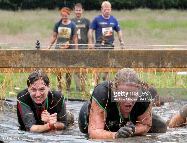Participants pass through the Electric Eel obstacle during the 2012 Tough Mudder Extreme Endurance Challenge held in the grounds of Drumlanrig Castle...