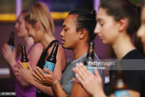Participants perform Beer Yoga stretches at a Beer Yoga class at The Emerson on July 11 2017 in Melbourne Australia Beer Yoga incorporates drinking a...