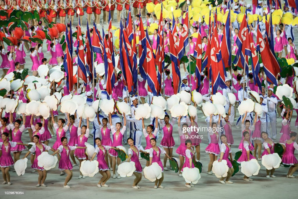 Participants perform in a 'Mass Games' artistic and gymnastic display at the May Day stadium in Pyongyang on September 9, 2018. - The biggest show on earth made a comeback as North Korea put on its its all-singing, all-dancing propaganda display, the 'Mass Games', for the first time in five years. Months in the preparation, the show featured tens of thousands of performers under the curved arches of the May Day Stadium, made up of 17,490 children simultaneously turning the coloured pages of books to create giant images rippling across one side of the stadium an analogue version, on a giant scale, of a usually digital solution to a digital demand.