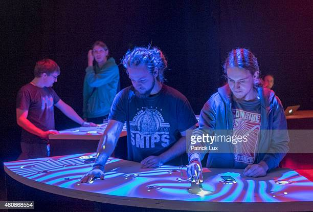 Participants play with a display built with beamers and sensors at the 31st annual Chaos Communication Congress on December 28 2014 in Hamburg...